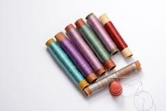 Placez pour la couture, les bobines multicolores avec des fils, l'aiguille et le dé sur le fond blanc Photo stock
