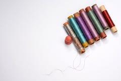 Placez pour la couture, les bobines multicolores avec des fils, l'aiguille et le dé sur le fond blanc Images libres de droits