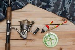 Placez pour pêcher sur le fond en bois avec l'habillement de camouflage Bobine, flotteurs colorés, ligne de pêche Photos stock