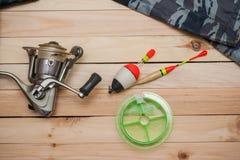 Placez pour pêcher sur le fond en bois avec l'habillement de camouflage Bobine, flotteurs colorés, ligne de pêche Photo stock