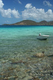 Placid Shoreline. This lonesome boat bobs gently on the quiet waves at Leinster Bay in St. John, USVI, just yards from the shoreline Stock Photos