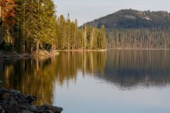 Calm shoreline of alpine lake with reflections of forest and mountains. Placid shoreline of alpine lake with reflections of forest and mountains Royalty Free Stock Photo