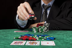 Placing a bet. A businessman placing a bet in a Texas hold 'em poker game Stock Images