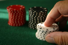 Placing a Bet. Close up of a hand placing a bet with poker chips Royalty Free Stock Photo
