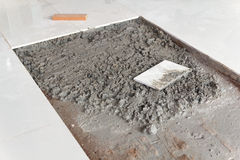 Placing ceramic floor tile in position over adhesive Royalty Free Stock Photography