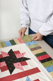 Placing cornerstone for quilt top border. A quilter arranges a square of fabric for the cornerstone of a quilt top border Stock Photos
