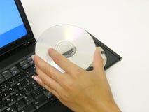 Placing A DVD. A photo of a woman placing a DVD into a laptop Stock Photos