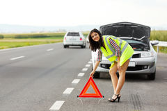 Placing Emergency Triangle. Woman in reflective vest placing emergency triangle in front of her broken car stock images