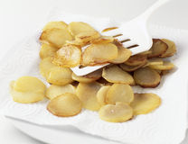 Placing the fried potatoes onto absorbing paper Royalty Free Stock Photo