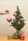 Placing gifts. Hands adding a present to the xmas tree Royalty Free Stock Photography