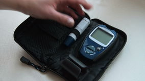 Placing glucometer and devices into case after blood sugar test stock video