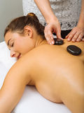 Placing hot stones during massage Stock Photos