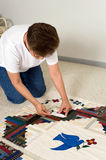Placing label on quilt. A quilter places a paper label on a panel of fabric prior to quilting Stock Photos