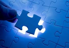 Placing last piece of jigsaw puzzle royalty free stock photo