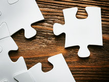 Placing missing a piece of puzzle. business concept. Wooden background Royalty Free Stock Photos
