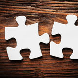 Placing missing a piece of puzzle. business concept. Wooden background Royalty Free Stock Photography