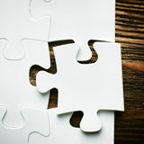 Placing missing a piece of puzzle. business concept. Wooden background Stock Photography