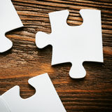 Placing missing a piece of puzzle. business concept. Wooden background Royalty Free Stock Images