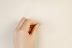 Placing nail against interior home wall Royalty Free Stock Image