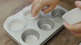 Placing paper cupcake liners into cupcake pan to bake cupcakes. 4K stock video footage