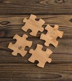 Placing a piece of the puzzle on a textured old wooden table. Conceptual work in the team and cooperation. idea of business Royalty Free Stock Images