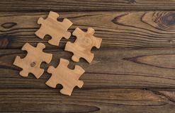 Placing a piece of the puzzle on a textured old wooden table. Conceptual work in the team and cooperation. idea of business Royalty Free Stock Photography
