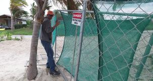 Placing protective fence near the beach,Bahamas stock video footage