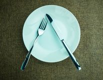 Placing a spoon. On a plate at a dining table royalty free stock photo