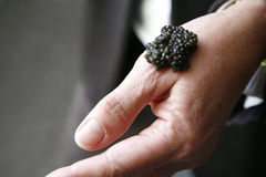 Placing a spoonful of caviar on a hand to taste Royalty Free Stock Photos
