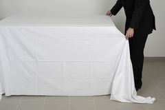 Placing a tablecloth on a buffet table Stock Image