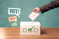 Placing a voting slip into a ballot box Stock Images