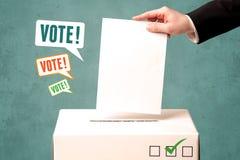 Placing a voting slip into a ballot box. A hand placing a voting slip into a ballot box Stock Photo