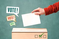 Placing a voting slip into a ballot box. A hand placing a voting slip into a ballot box Royalty Free Stock Image