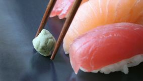 Placing wasabi on Platter. Placing ball of wasabi on platter with tuna and salmon nigiri sushi rolls stock video
