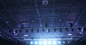 Plafond au concert avec les projecteurs blancs et bleus banque de vidéos