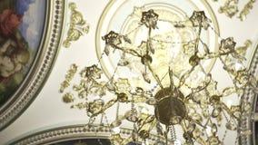 Plafond des fresques avec le lustre en cristal longueur Vue de dessous sur le plafond frescoed illuminé en égalisant la lumièr banque de vidéos