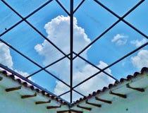 Plafond en verre avec le ciel bleu et les nuages blancs Photo stock