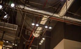 Plafond in stedelijke stijlzolder met kettingen, grote projectoren en zilverachtige pijpen royalty-vrije stock afbeelding