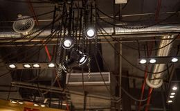 Plafond in stedelijke stijlzolder met kettingen, grote projectoren en zilverachtige pijpen royalty-vrije stock afbeeldingen
