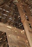 Plafond van een instortend houten landbouwbedrijfgebouw met zonlicht en schaduwpatronen Royalty-vrije Stock Foto