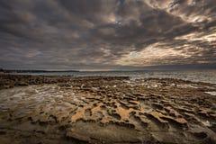 Plage à marée basse de plage pierreuse dans le matin photographie stock