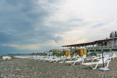 Plage abandonnée avec des canapés du soleil avec un jour nuageux En prévision de la saison de plage photographie stock libre de droits
