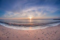 Plage arénacée de mer de paysage au coucher du soleil avec le soleil au-dessus de l'horizon photo stock