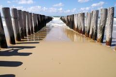 Plage atlantique avec les ondes de rupture en bois de pôles Photographie stock libre de droits