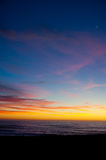 Plage au coucher du soleil avec la lune photographie stock libre de droits