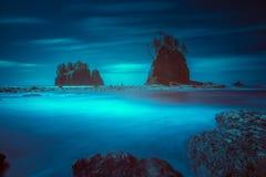 Plage avec des piles de mer dans l'éclairage déprimé Images stock