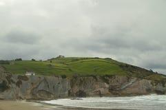Plage avec des roches composées de disques de fossile avec des formations du type de flysch de l'UNESCO Basque paléocène d'itinér images libres de droits