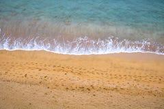 Plage avec la vague bleue claire et empreintes de pas en sable Photo libre de droits
