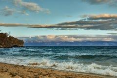 Plage azurée avec de l'eau les montagnes pierreuses et clair de Baikal un jour nuageux photographie stock libre de droits