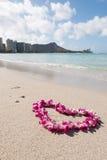 Plage blanche de sable de mer d'orchidée de guirlande en forme de coeur de fleur Image stock